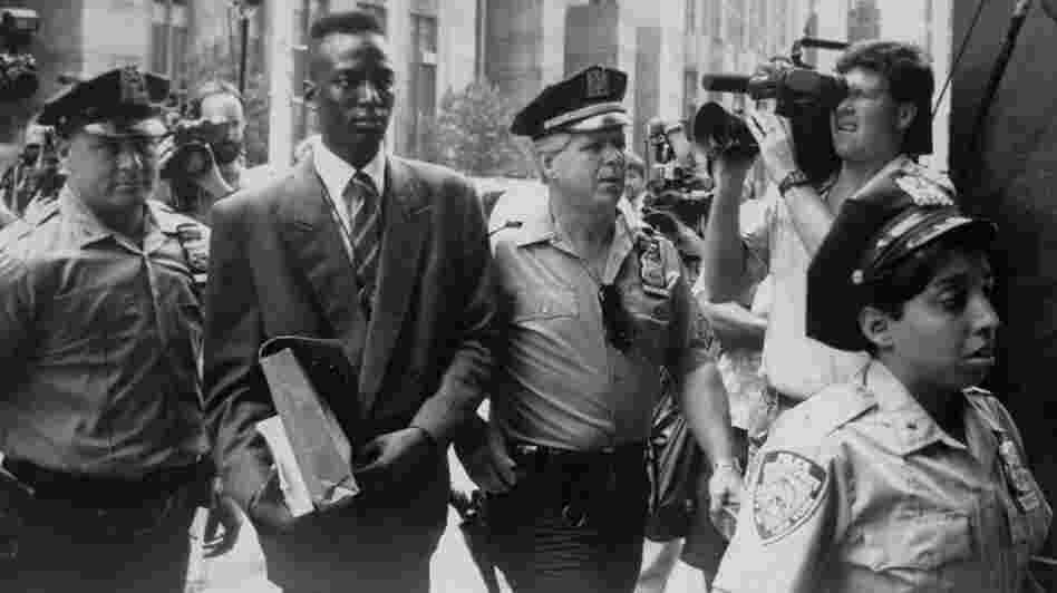 Yusef Salaam, wrongly accused of rape, is escorted by police. He and four other teens were eventually found guilty of a crime they didn't commit.