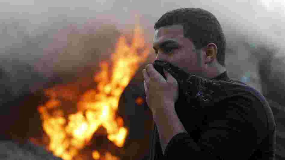 A man covers his face as he passes smoke and fire after Israeli air strikes in Gaza City earlier today.