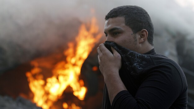 A man covers his face as he passes smoke and fire after Israeli air strikes in Gaza City earlier today. (AFP/Getty Images)
