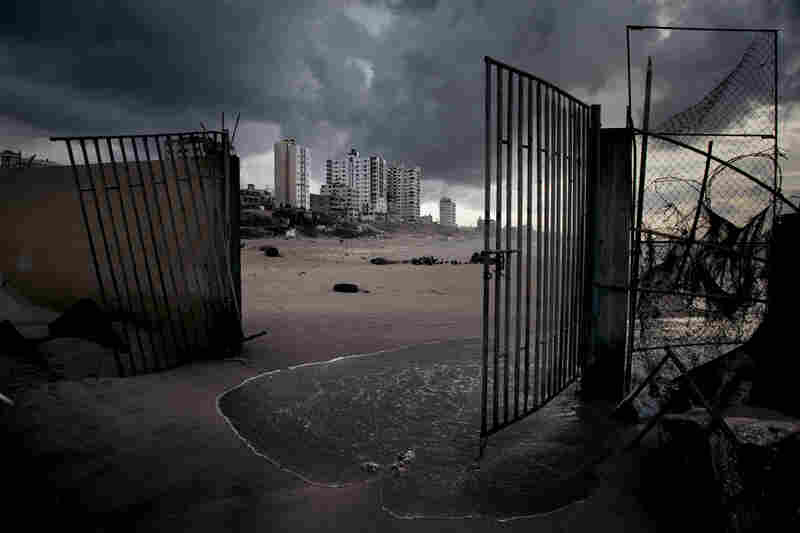 Gaza City apartments rise beyond the broken gates of a waterfront restaurant. The beach once bustled with fishing boats and cafes, but the Israeli naval blockade, sewage and lack of resources for rebuilding have taken their toll.