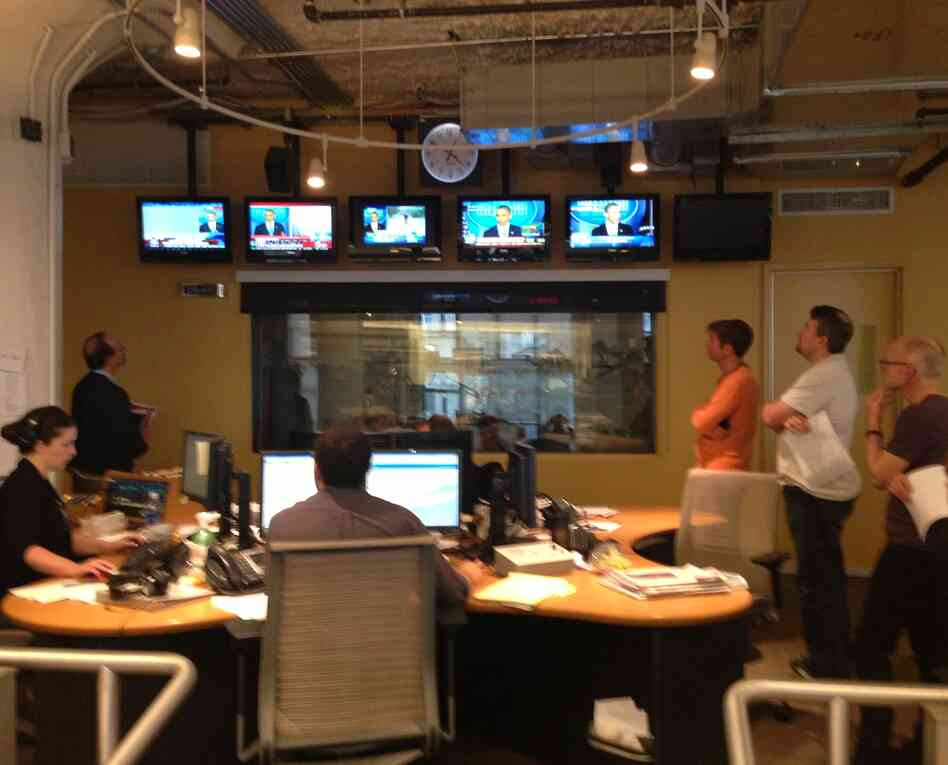 WNYC staff in generator-powered newsroom watch President Obama speaking from the White House about Sandy. (L-R) Reporter Brigid Bergin, Brian Lehrer, producer Javier Guzman (back to camera), host Richard Hake, host Lance Luckey, and VP-News Jim Schachter.
