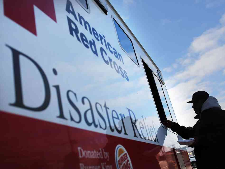 People receive free food from the American Red Cross in the heavily damaged Rockaway neighborhood on Nov. 14, 2012 in the Queens borough of New York City.