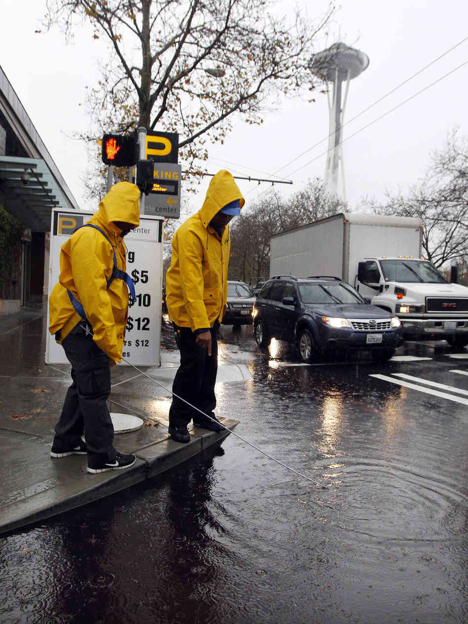 Parking attendants search for a clogged drain in S