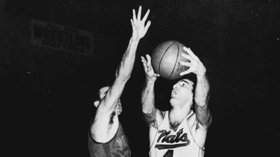 Dolph Schayes (right) of the Syracuse Nationals drives in to score in a March 1959 NBA playoff game. (AP)