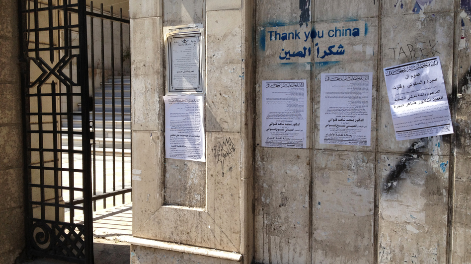 Death notices hang on a wall alongside pro-regime graffiti in central Damascus. (Courtesy)