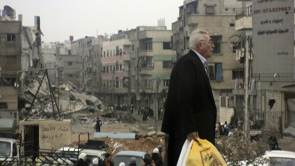 A man walks near buildings damaged after shelling by forces loyal to Syria's President Bashar Assad, at Harasta, a suburb of Damascus, on Nov. 19.