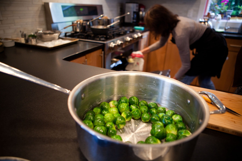 Food stylist Lisa Cherkasky, who cooked most of the meal in advance of the taping, checks the temperature on the oven. The trick to Child's Brussels sprouts is to blanch them first, then cut off the ends and place them flat on the bottom of the pan so they soak up all the butter. (Maggie Starbard/NPR)