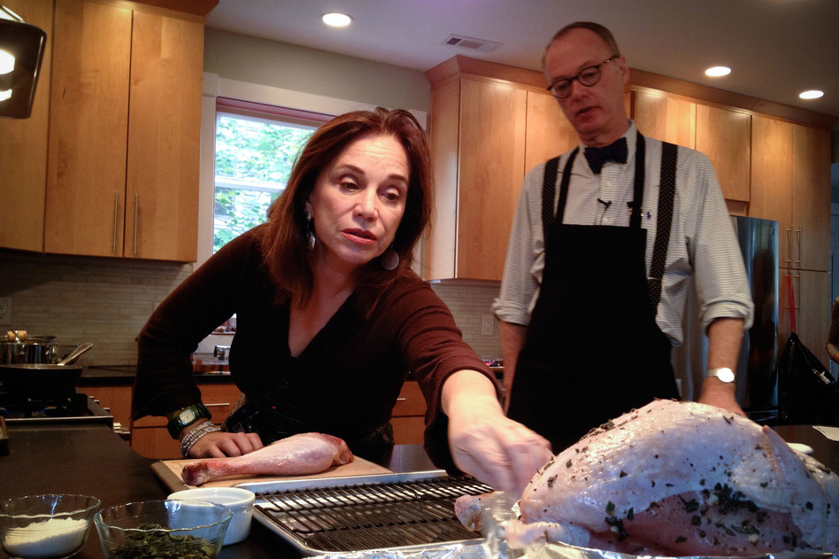 Morning Edition's RenŽee Montagne reaches for the prepared turkey as Kimball explains how Child's recipe calls for the turkey breast to be butterflied and separated from the thighs and legs and cooked in different pans. (Maggie Starbard/NPR)