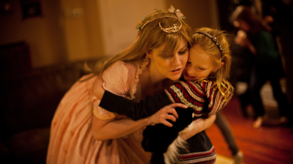 "Mary Alice LeGrow, otherwise known as ""Princess Marty,"" hugs a young girl during a birthday party in a Philadelphia suburb. A graphic artist and ""cosplay"" (costume play) fanatic, LeGrow became a full-time professional party princess to make ends meet during the economic downturn. (NPR)"