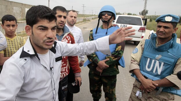 Supporters of President Bashar Assad speak with U.N. monitors who were arriving in the town in May. The monitors have since left.