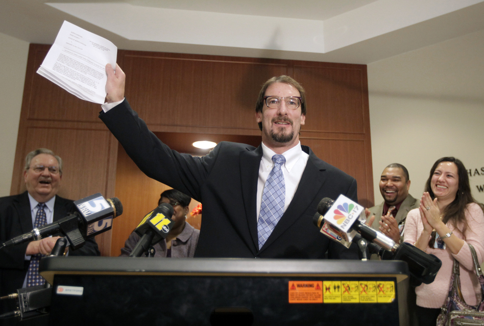 Greg Taylor holds up his release papers after he was unanimously exonerated by a three-judge panel in Raleigh, N.C., in 2010. Taylor, who had been in prison since 1993 for murder, is now suing several people who worked at a crime lab, claiming their  erroneous findings landed him in jail. (Shawn Rocco/AP)