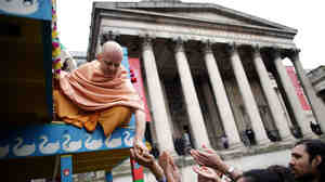 A Hare Krishna distributes food gifts from a chariot during a festival in London in 2011. The religious group began distributing books, flowers and gift