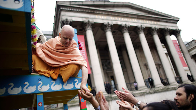A Hare Krishna distributes food gifts from a chariot during a festival in London in 2011. The religious group began distributing books, flowers and gifts to strangers in the 1970s, drawing on the rule of reciprocation to raise money. (Getty Images)