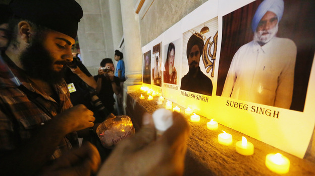 Photos of victims are seen during a candlelight vigil in Union Square for victims of the Wisconsin Sikh temple shooting on August. (Getty Images)