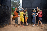 Boys hang out by the gate guarding the Kabanga Protectorate Center, as a local village girl walks by outside, in Kabanga, Tanzania.