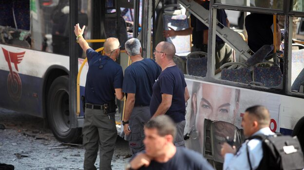 Israeli police and rescue personnel at the scene of the bus bombing in central Tel Aviv today.