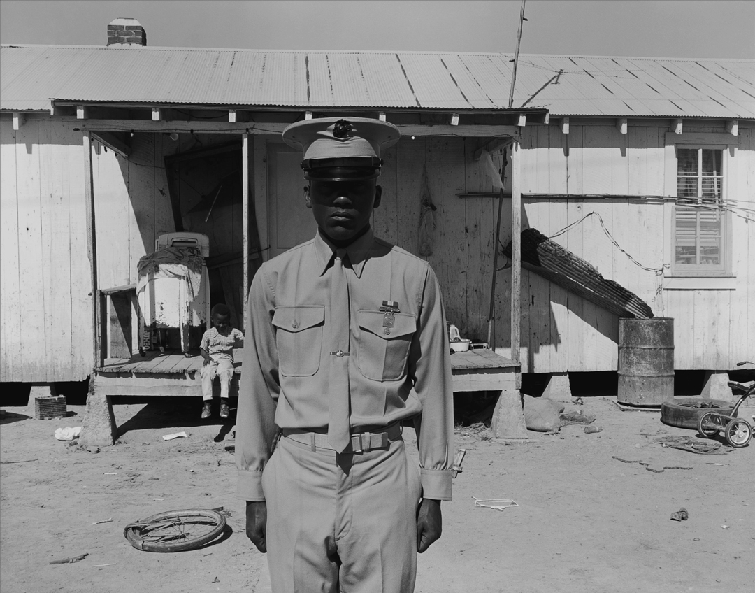 """A young Marine on an R&R leave from the military visits his home, a sharecropper shack, in 1970 in Hughes, Ark."""