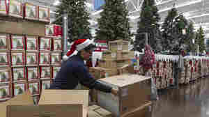 Walmart associate Angel Campos stocks Christmas decorations Wednesday ahead of the pre-Black Friday event at the Wal-Mart Supercenter store in Rosemead, Calif.