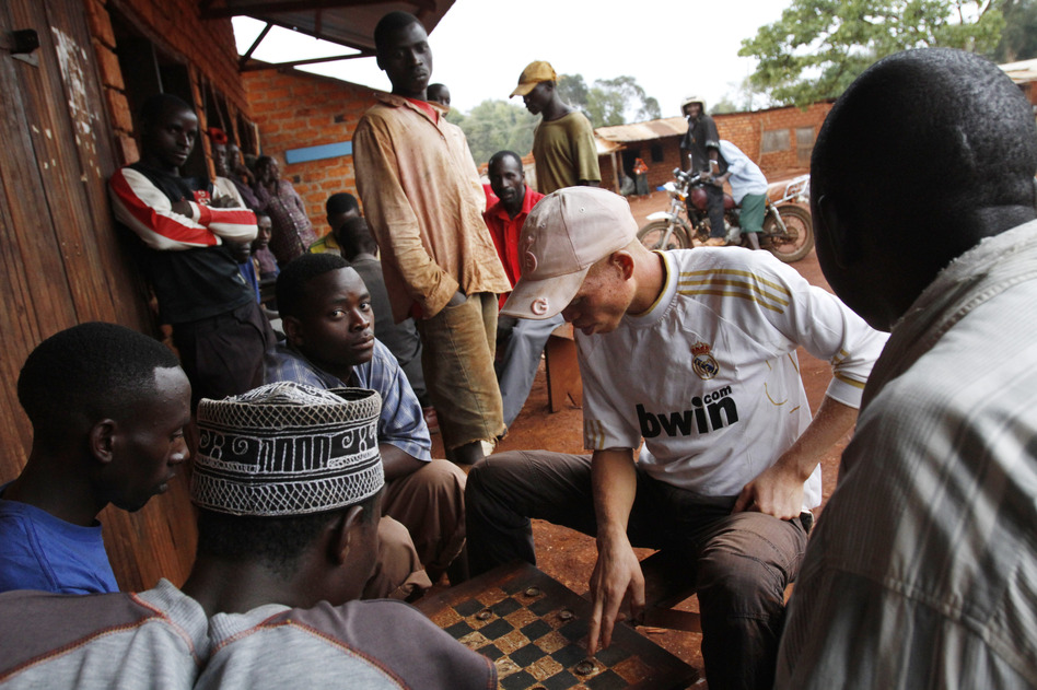 Maajabu Boaz, 20, who has albinism, plays checkers with local men where he feels safe in Nengo Village, Kibondo, Tanzania. Boaz has a reputation of carrying knives for self-protection. (Jacquelyn Martin for NPR)