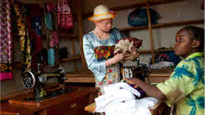 Angel Salvatory, 17, buys cloth at a market in Kabanga village in Tanzania. Albinos living in a nearby protection center are allowed to go to the local market as long as they travel in a group for their own safety.
