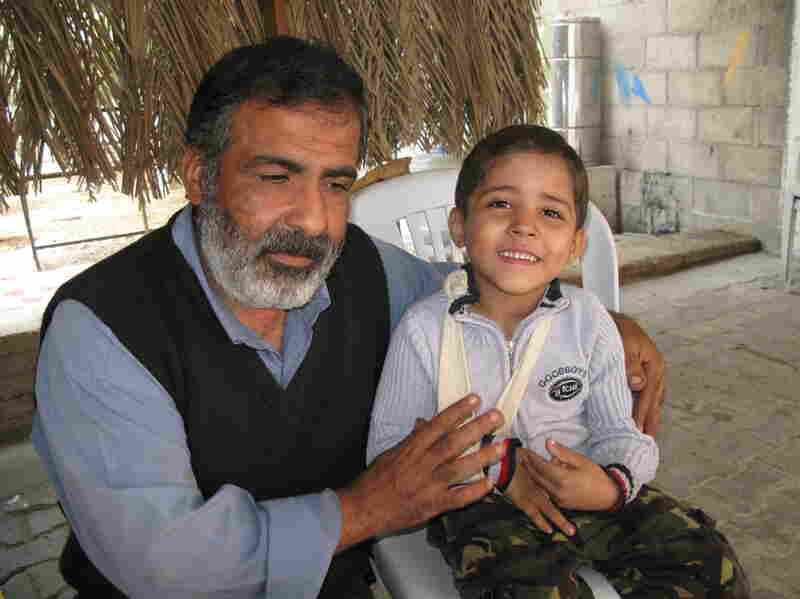 Osama Qurtom and his son Mahmoud at their home in Gaza.