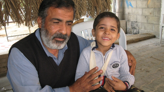 Osama Qurtom and his son Mahmoud at their home in Gaza. (NPR)
