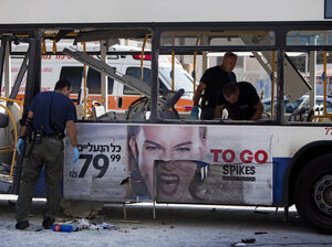 Israeli police officers examine a blown up bus at the site of a bombing in Tel Aviv on Wednes