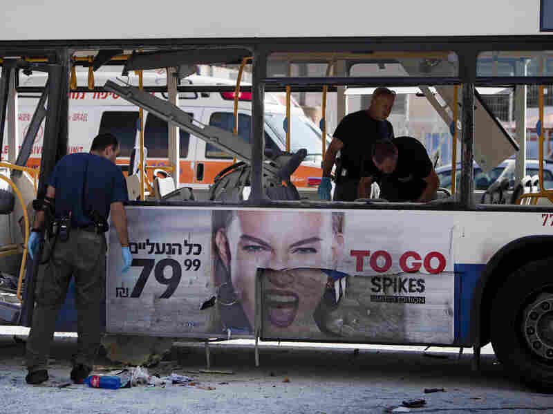 Israeli police officers examine a blown up bus at the site of a bombing in Tel Aviv on Wednesday.