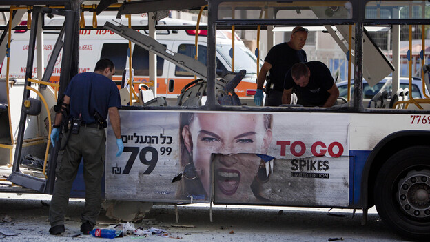 Israeli police officers examine a blown up bus at the site of a bombing in Tel Aviv on Wednesday. (AP)
