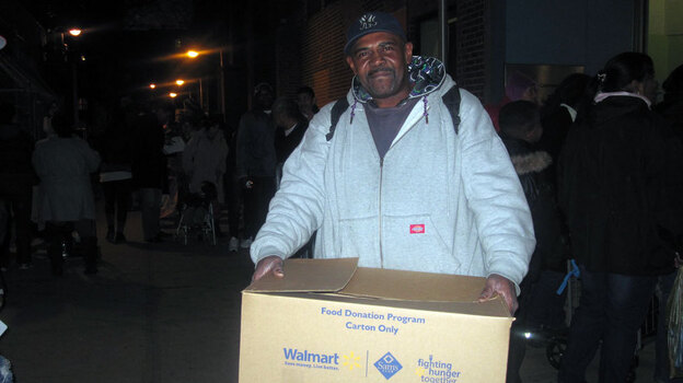 Maurice Geddie of Brooklyn's Red Hook neighborhood picks up a free turkey donated by a local grocery store. He's hoping his wife will be willing to cook it, though she's been stuck cooking for storm victims at shelters for weeks. (NPR)