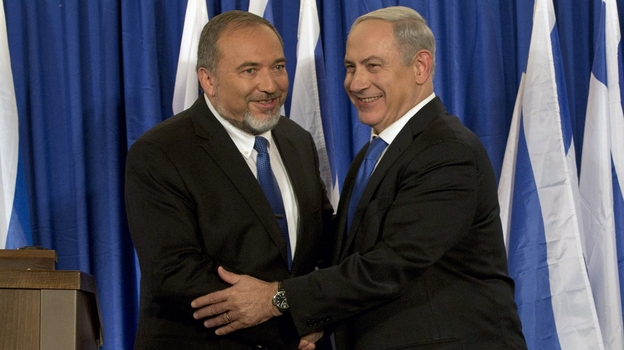 Israeli Prime Minister Benjamin Netanyahu (right) and Foreign Minister Avigdor Lieberman shake hands in front of the media after giving a statement in Jerusalem last month. Netanyahu said his Likud Party will join forces with the hard-line party of his foreign minister in upcoming parliamentary elections. (AP)