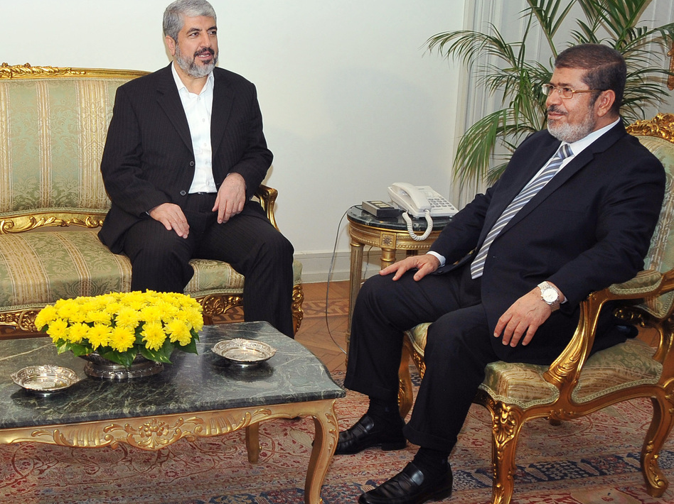 In this image provided by Egyptian President Mohammed Morsi (right), Hamas leader Khaled Mashaal meets with Morsi at the Presidential Palace in Cairo on Sunday. Morsi has won praise for brokering the cease-fire agreement between Hamas and Israel.