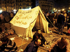 "Pro-democracy demonstrators occupy Cairo's Tahrir Square on Friday night. The writing on the tent reads, ""Egypt is not a farm, Constitution party, Egypt for Egyptians."""