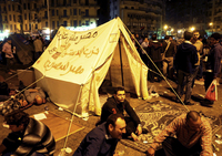 Pro-democracy demonstrators occupy Cairo's Tahrir Square on Friday night. The writing on the tent reads,