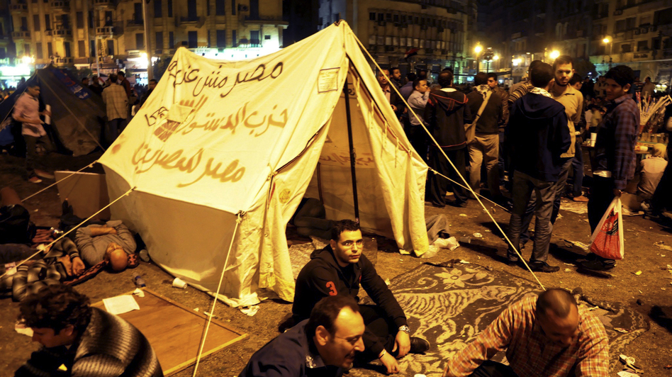 "Pro-democracy demonstrators occupy Cairo's Tahrir Square on Friday night. The writing on the tent reads, ""Egypt is not a farm, Constitution party, Egypt for Egyptians."" (AP)"