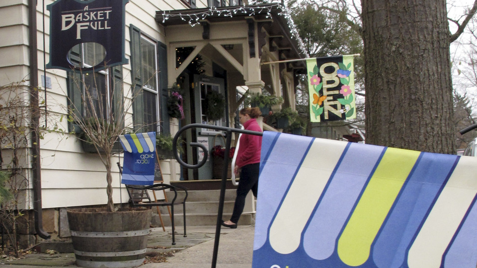A flag urges customers to shop locally near a store in Boalsburg, Pa., on Friday. Owners of small stores hope to get a boost from Small Business Saturday. (AP)