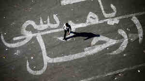 "An Egyptian man walks over a graffiti reading ""Mor"