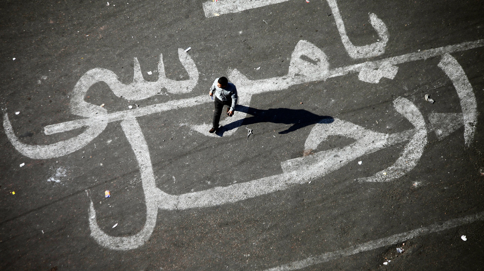 "An Egyptian man walks over a graffiti reading ""Morsi Go"" at Egypt's landmark Tahrir square in Cairo. (AFP/Getty Images)"