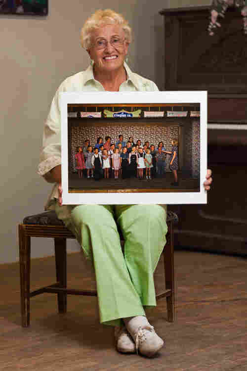 Kathryn Roberts at the Pie Town Community Center (formerly the Farm Bureau), holding the photo of her class singing