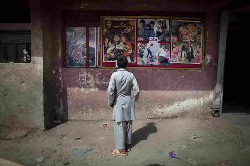 A young Afghan boy looks at movie posters outside Temorshahee Cinema in Kabul. Going to the movies, once banned under the Taliban, has become a popular form of entertainment in Kabul, but women and children rarely take part.