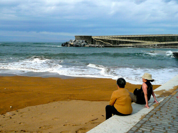 Residents of Mutriku, a fishing village on Spain's northern coast, lounge at their local beach, protected from fierce Atlantic waves by a cement breakwater that also houses Europe's