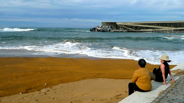 Residents of Mutriku, a fishing village on Spain's northern coast, lounge at their local beach, protected from fierce Atlantic waves by a cement breakwater that also houses Europe's first wave energy plant. (Lauren Frayer for NPR)