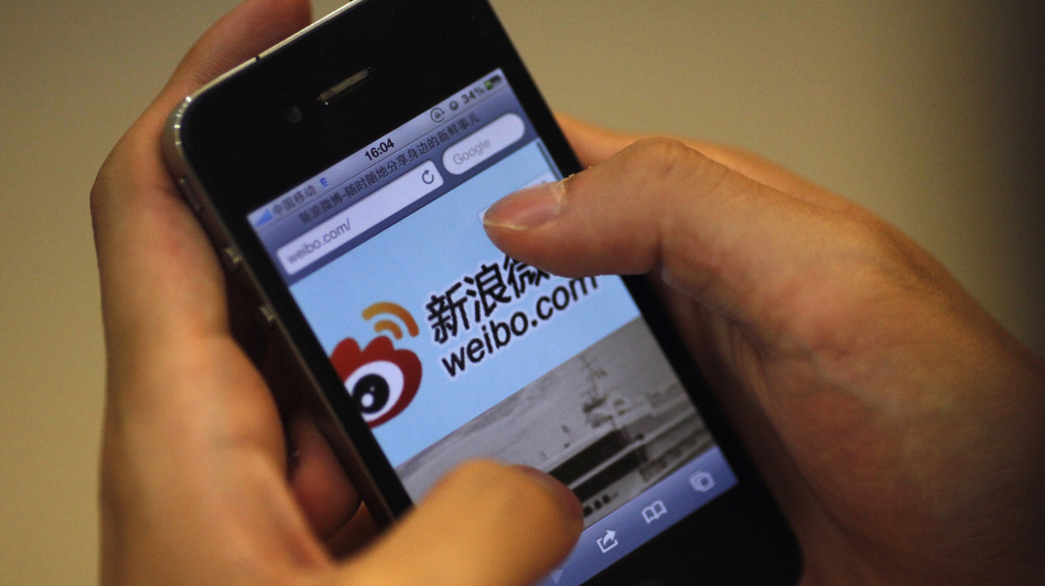 A man holds an iPhone as he visits Sina's Weibo microblogging site in Shanghai earlier this year. (Reuters/Landov)