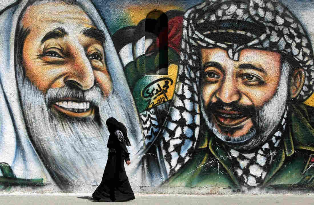 A Palestinian woman walks past a mural d