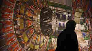 A worker walks past a giant photograph of the CMS detector of the Large Hadron Collider (LHC) at a 2008 science exhibition in Berlin, Germany.