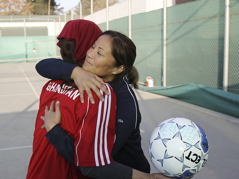 Former U.S. Olympian Lorrie Fair hugs Zahra Mahmoudi, the captain of the Afghan women's soccer team.