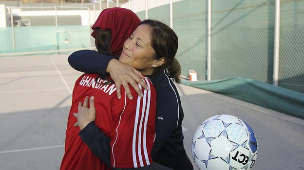 Former U.S. Olympian Lorrie Fair hugs Zahra Mahmoudi, the captain of the Afghan women's soccer team. (NPR)