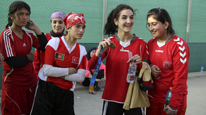 Afghan soccer player Hadissa Wali holds the Olympic medal belonging to former U.S. player Lorrie Fair.