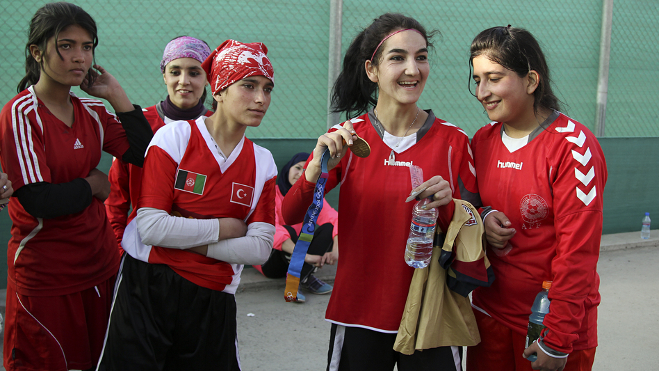 Afghan soccer player Hadissa Wali holds the Olympic medal belonging to former U.S. player Lorrie Fair. (NPR)