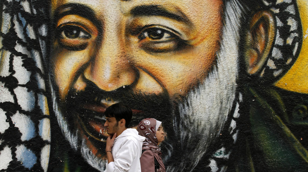 Palestinians walking in front of a mural of late Palestinian leader Yasser Arafat in Gaza City earlier today.